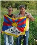 Pierre et une bénévole, exibant le drapeau du Tibet